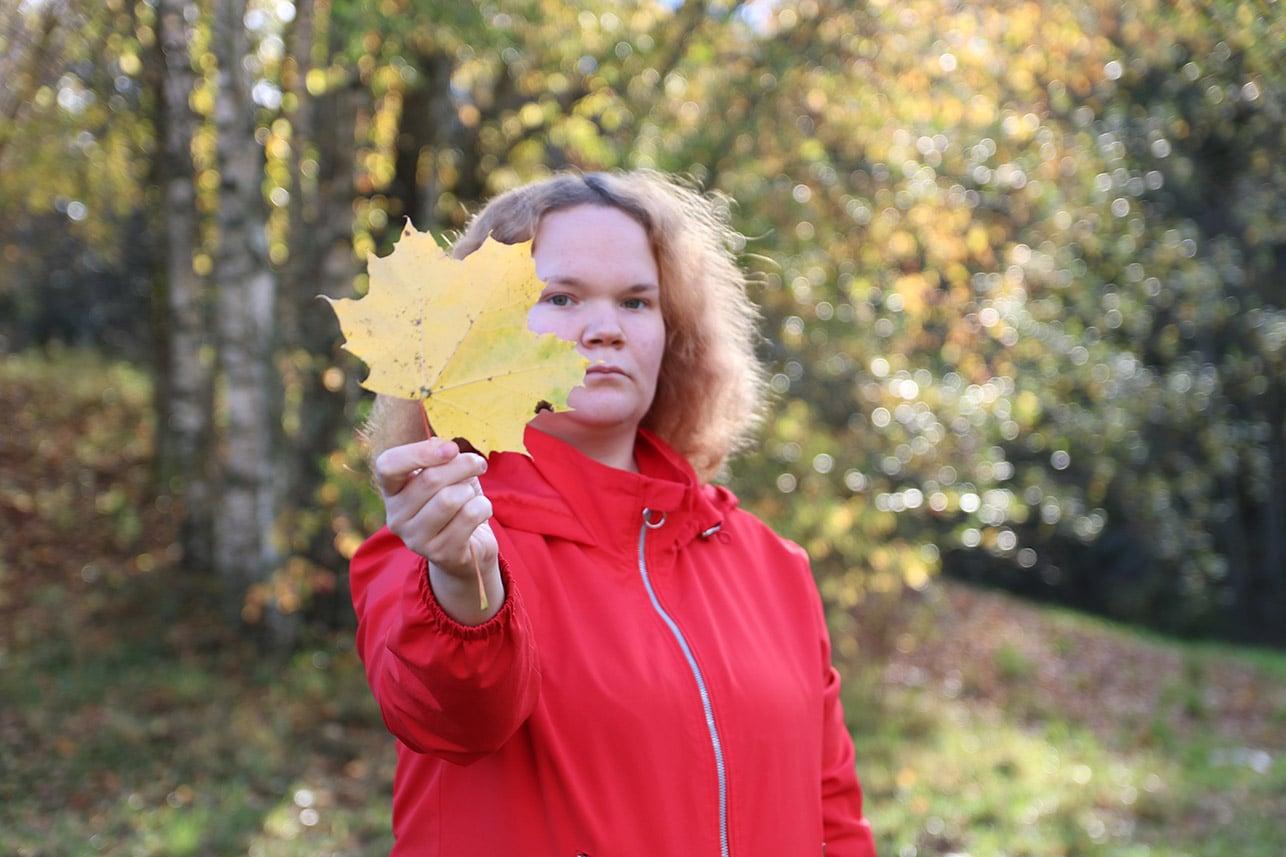 Punaiseen takkiin pukeutunut nainen pitää vaahteran lehteä kädessä kohti kameraa.