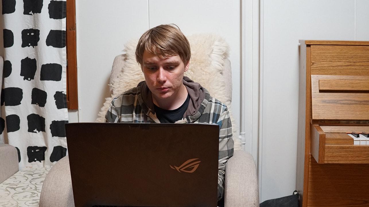 Ville istuu kotinsa nojatuolissa kannettavan tietokoneen äärellä.