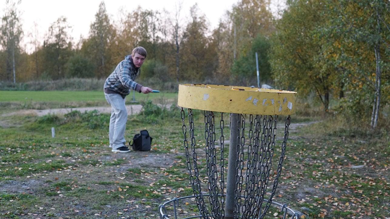 Ville pelaa ulkona frisbeegolfia.