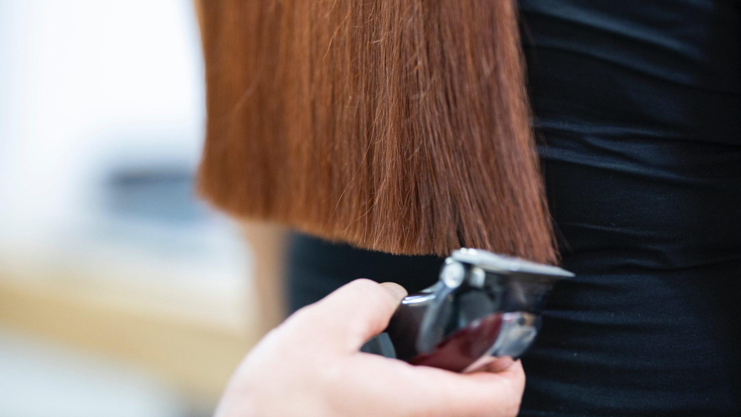 Kampaaja tasaa tummahiuksisen naisen hiuksia koneella.