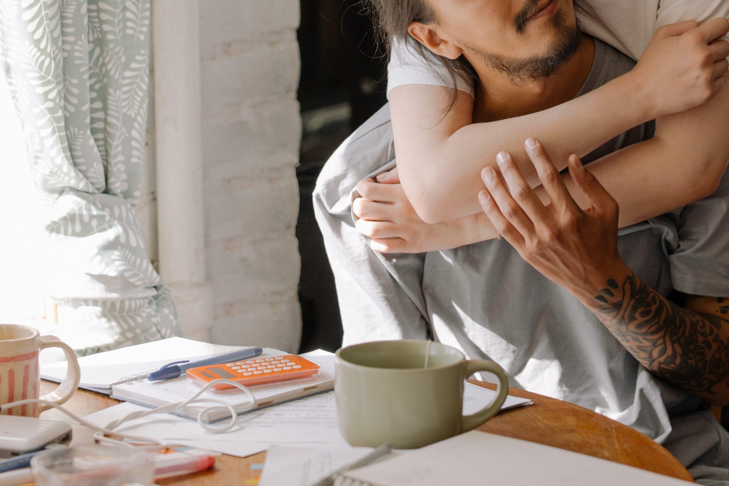 Mies istuu keittiönpöydän ääressä, nainen halaa häntä takaa, kädet kietoutuneena miehen kaulan umpärille. Mies katsoo viistosti halaavaa naista. Pöydällä kahvikuppi, kyniä, laskin ja muistivihko.