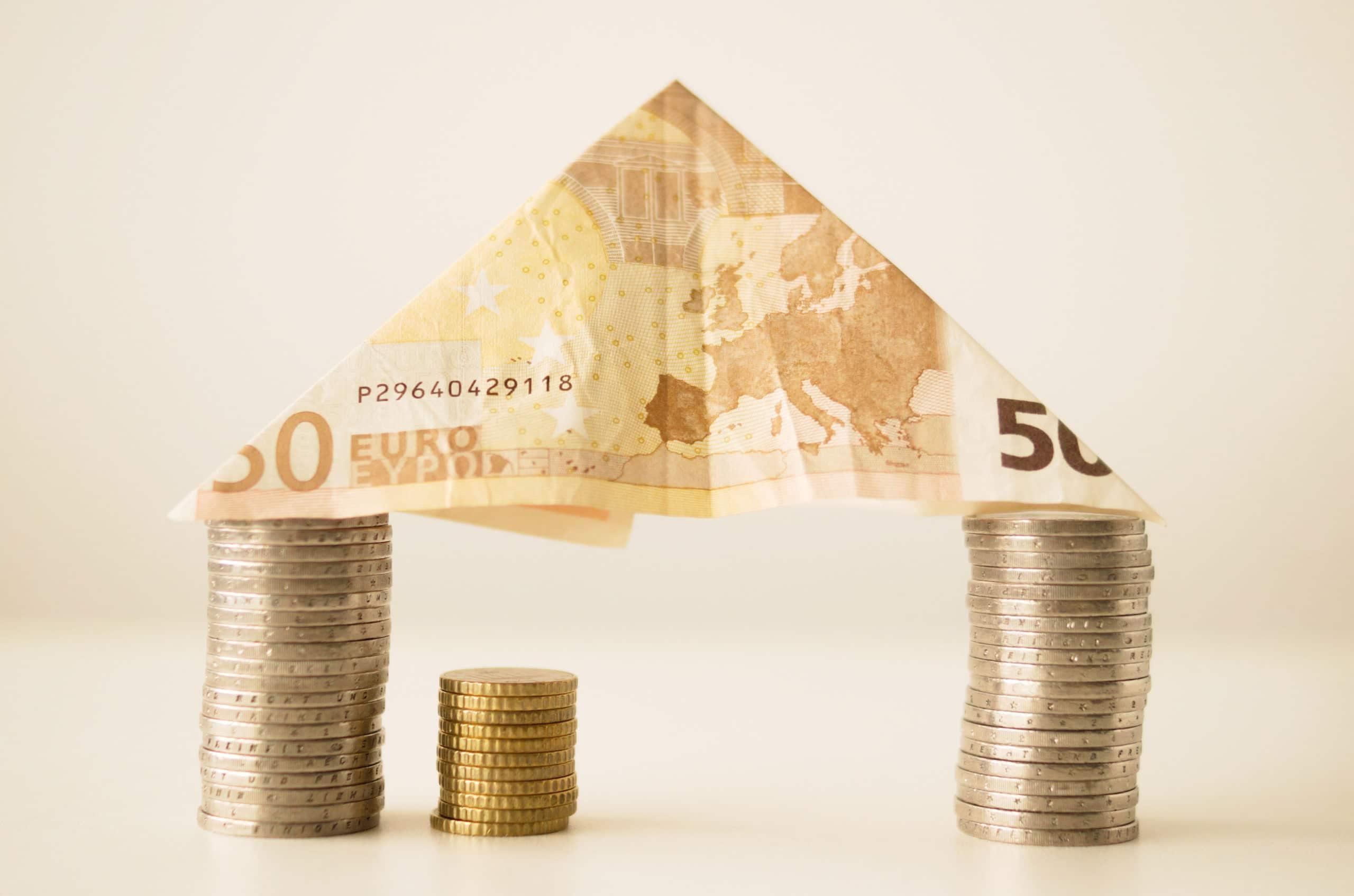Kaksi kolikkopinoa, joiden päällä kolmioksi taiteltu viidenkymmenen euron seteli.